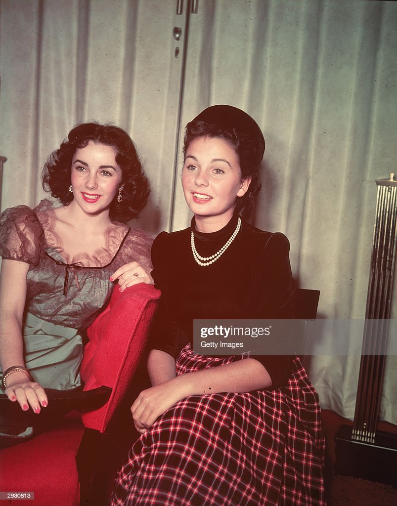 British-born actors Elizabeth Taylor (L) and Jean Simmon sit together and smile, circa 1940s.
