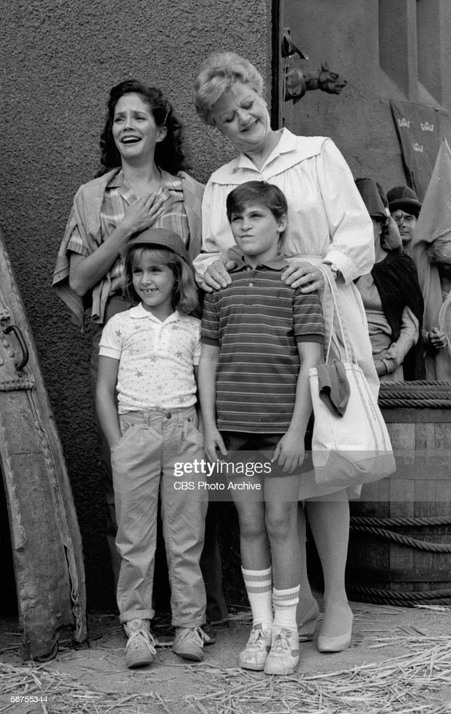 British-born actress Angela Lansbury (rear right) smile down at American sibling child actors Summer Phoenix and <a gi-track='captionPersonalityLinkClicked' href=/galleries/search?phrase=Joaquin+Phoenix&family=editorial&specificpeople=215391 ng-click='$event.stopPropagation()'>Joaquin Phoenix</a> (1970 - 1993), while actress Anne Kerry (left) expresses relief in a scene from an episode from the television series 'Murder, She Wrote' titled 'We're Off to Kill the Wizard,' California, August 20, 1984.