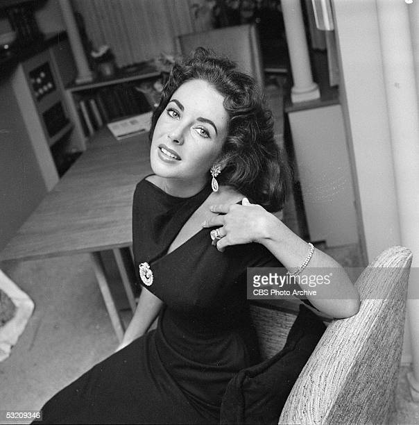 Britishborn actress Elizabeth Taylor poses with her head thrown back in her home Berverly Hills California February 20 1957 She is wearing a dress...