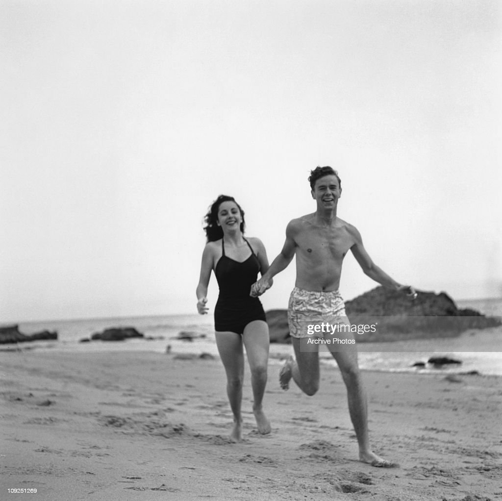 British-born actress <a gi-track='captionPersonalityLinkClicked' href=/galleries/search?phrase=Elizabeth+Taylor&family=editorial&specificpeople=69995 ng-click='$event.stopPropagation()'>Elizabeth Taylor</a> runs along a beach with her friend, actor Marshall Thompson (1925 - 1992), circa 1948.