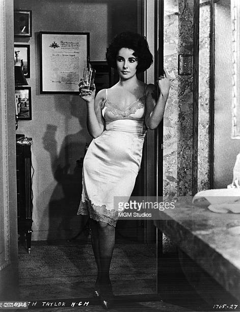 Britishborn actress Elizabeth Taylor stands in a doorway and wears slip as she holds a glass in a still from the film 'BUtterfield 8' directed by...