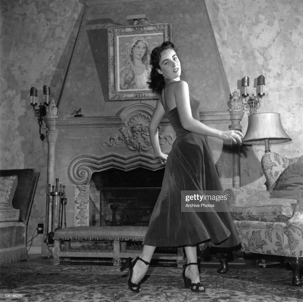 British-born actress Elizabeth Taylor wearing a velvet evening dress and high-heeled shoes, circa 1950.