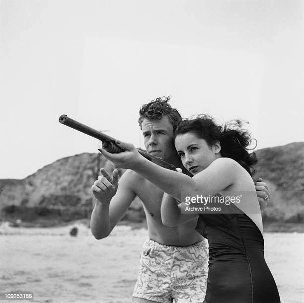 Britishborn actress Elizabeth Taylor with a gun on the beach circa 1948 She is with her friend actor Marshall Thompson