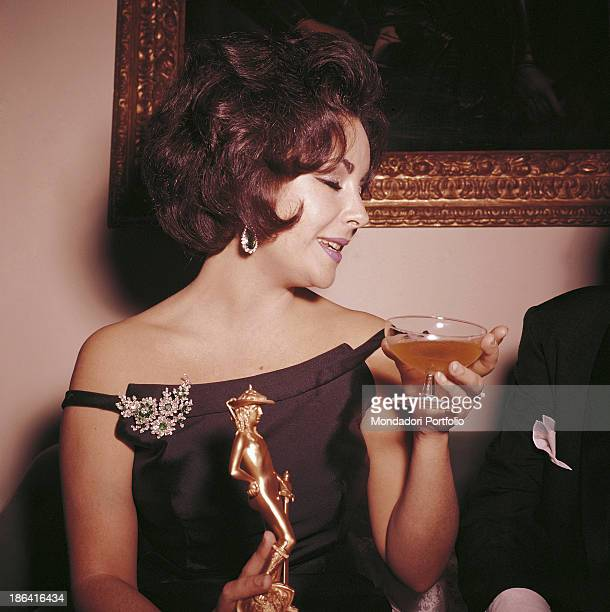 Britishborn American actress Elizabeth Taylor having a drink holding the David di Donatello Award in her hand won for her performance in the film...