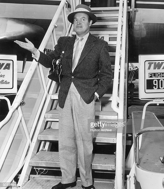 Britishborn American entertainer Bob Hope standing in front of a TWA airplane stairway holding out his hand as if it were about to rain at Idlewild...