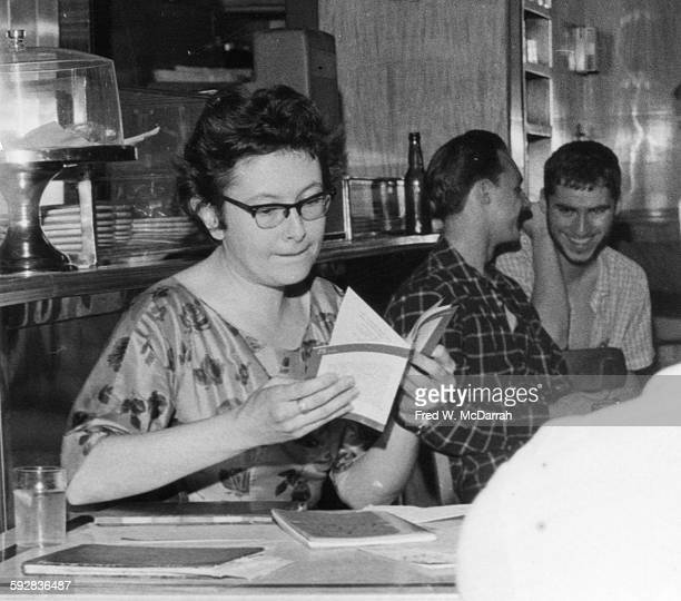 Britishborn American poet Denise Levertov reads a book in the Nicholas Cafe New York New York June 21 1959