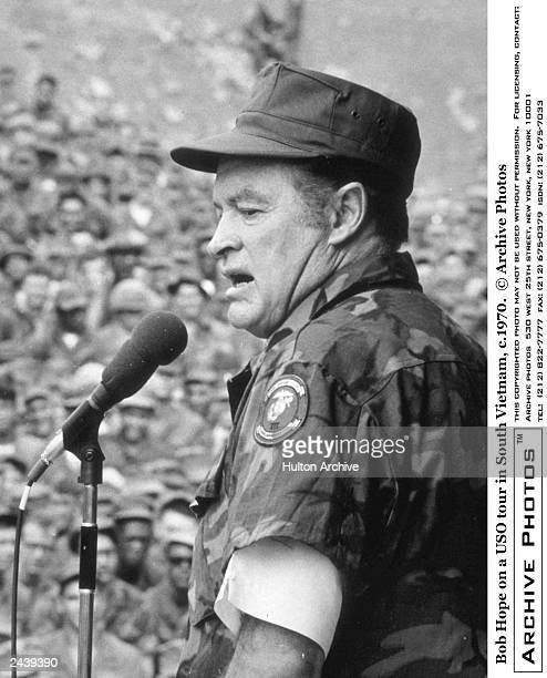 Britishborn entertainer Bob Hope wearing a camouflage uniform stands at a microphone speaking before a crowd of US troops on a USO tour in South...