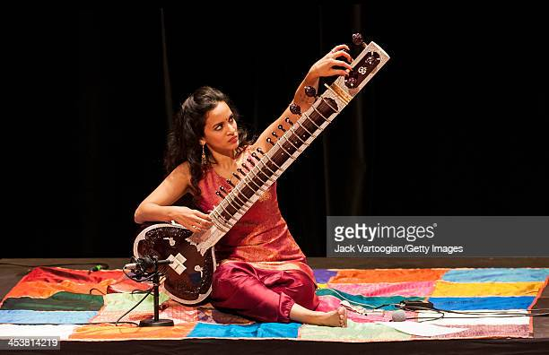 Britishborn Indian musician Anoushka Shankar tunes her sitar during a perfromance with her ensemble at a World Music Institute concert at New York...