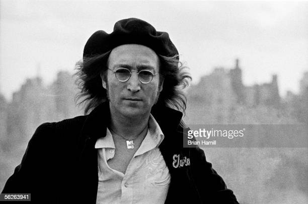 Britishborn singer and songwriter John Lennon in front of an unfocused cityscape on the roof of his apartment building the Dakota New York New York...