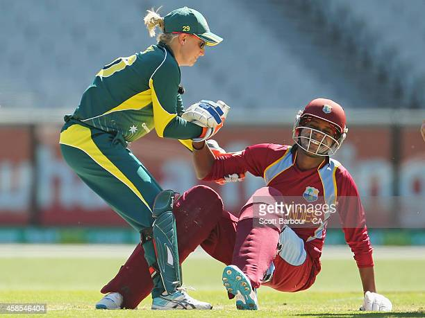 Britney Cooper of the West Indies is helped to her feet by wicketkeeper Alyssa Healy of Australia after being dismissed first ball during game three...