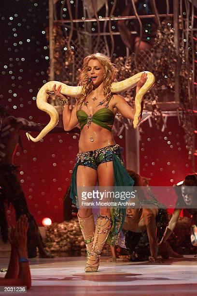 Britney Spears performs on stage with a snake wrapped around her neck at the 2001 MTV Video Music Awards held at the Metropolitan Opera House at...