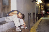 young man vomiting on the pavement after getting drunk on night out in San Antonio Ibiza