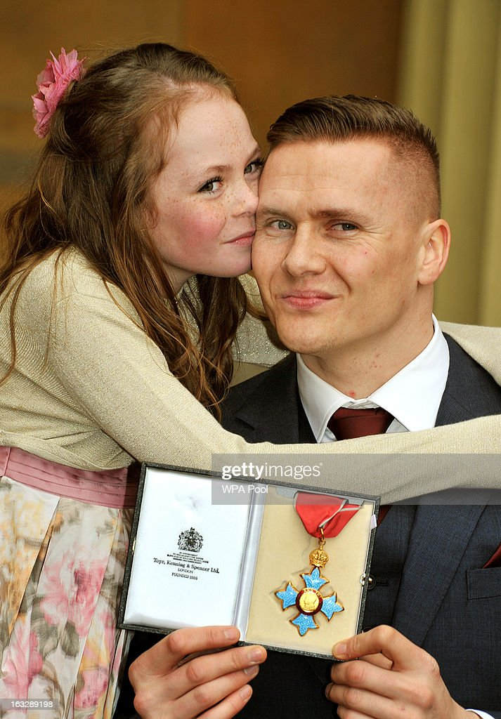 Britsish Paralympian and six-times Paralympic gold medalist David Weir proudly holds his CBE award with his daughter Ronie, after the Investiture Ceremony at Buckingham Palace on March 07, 2013 in London, England.