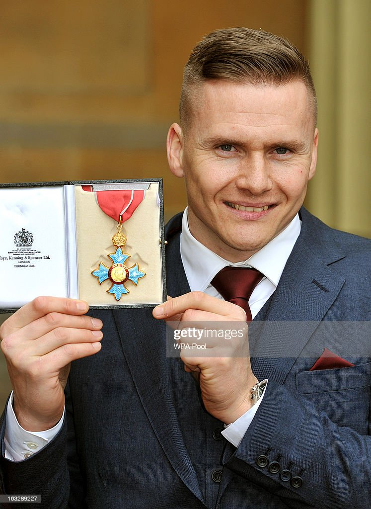 Britsish Paralympian and six-times Paralympic gold medalist David Weir proudly holds his CBE award after the Investiture Ceremony at Buckingham Palace on March 07, 2013 in London, England.