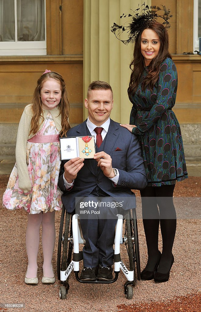 Britsish Paralympian and six-times Paralympic gold medalist David Weir proudly holds his CBE award with his wife Emily and daughter Ronie after the Investiture Ceremony at Buckingham Palace on March 07, 2013 in London, England.