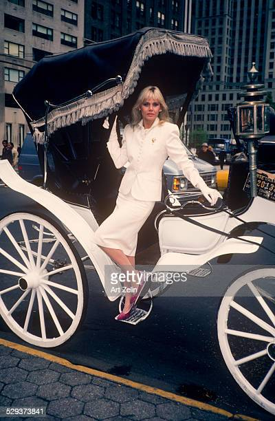 Britt Ekland posing in a white suit standing in a Hansom Cab circa 1970 New York