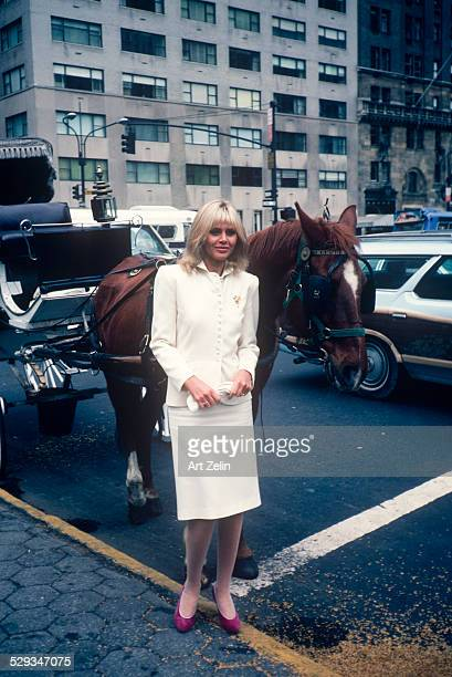 Britt Ekland posing with the horse of a Hansom Cab wearing a white suit circa 1970 New York