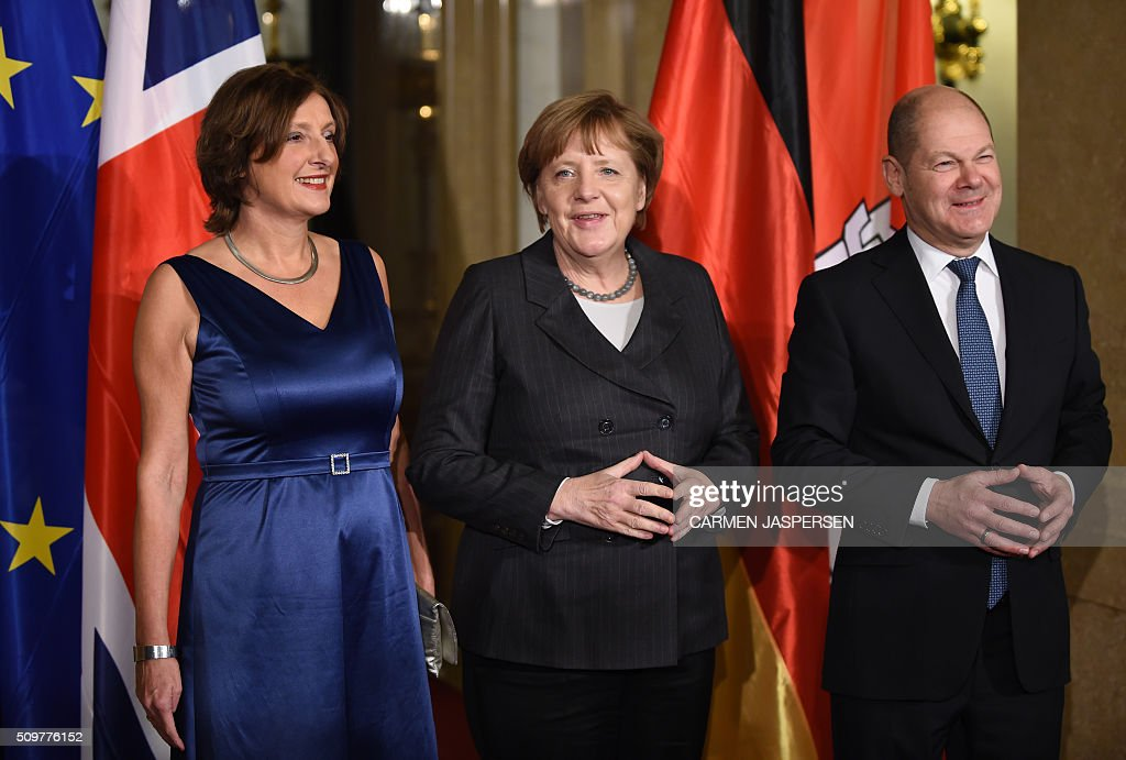 Britta Ernst (l) wife from Olaf Scholz (r), Mayor of Hamburg, German Chancellor Angela Merkel pose for a photo at the Matthiae-Mahl Dinner in Hamburg, northern Germany on February 12, 2016. / AFP / CARMEN JASPERSEN