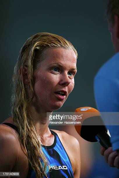 Britta Steffen of Germany speaks to the media after competing during the Swimming Women's 100m Freestyle preliminaries heat six on day thirteen of...
