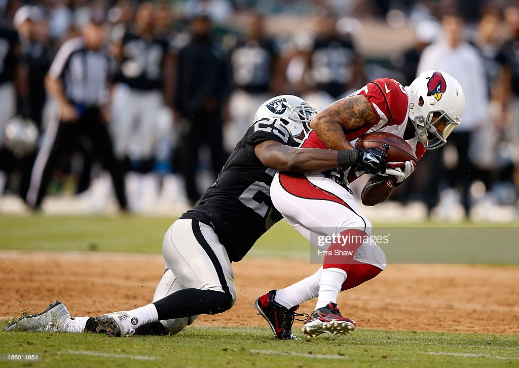 Brittan Golden of the Arizona Cardinals is tackled by DJ Hayden of the Oakland Raiders at Oco Coliseum on August 30 2015 in Oakland California