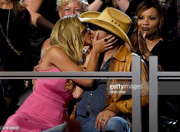 Brittany Kerr kisses her husband recording artist Jason Aldean after he won the award for Male Vocalist of the Year during the 50th Academy of...
