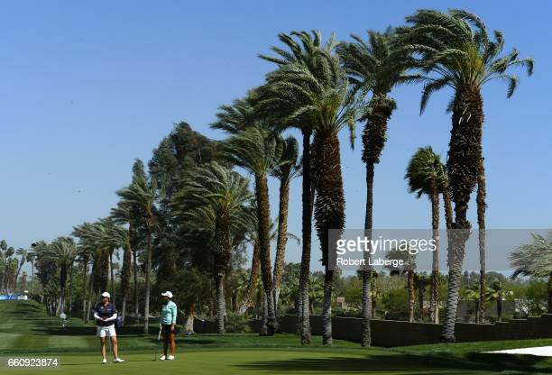 Brittany Lincicome and Lydia Ko of New Zealand wait to play on the 15th green as the wind picks up during round one of the ANA Inspiration on the...