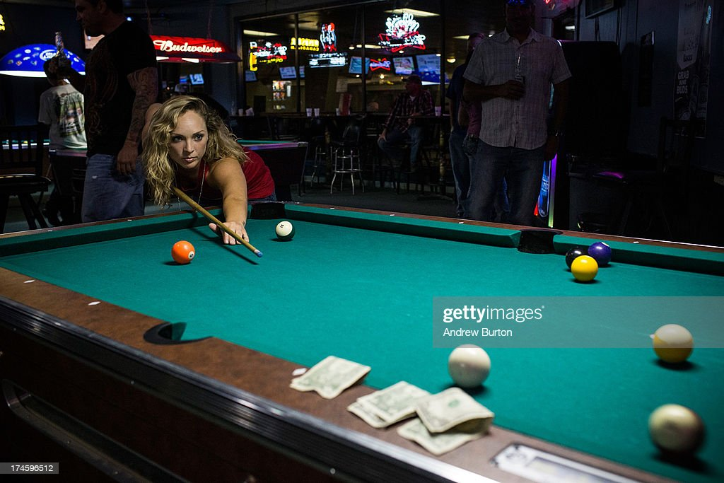 Brittany Paige, originally from California, plays a game of pool at a bar on July 27, 2013 in Williston, North Dakota. The western region of North Dakota has seen a rise in crime, automobile accidents and drug usage recently, due in part to the oil boom which has brought tens of thousands of jobs to the region, lowering state unemployment and bringing a surplus to the state budget.