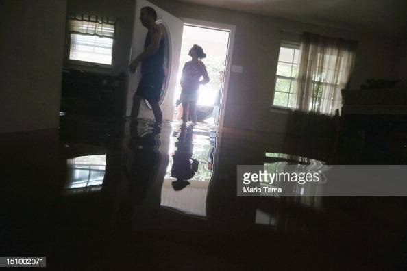 Brittany Trumbaturi prepares to leave her flooded home with family member Joshua Barbot who came to rescue family members in a boat on August 30 2012...