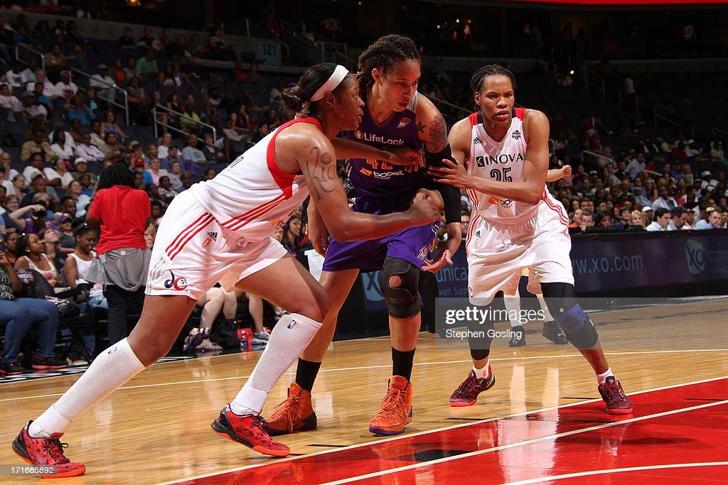 Brittney Griner of the Phoenix Mercury prepares to rebound against Kia Vaughn and Monique Currie of the Washington Mystics at the Verizon Center on...