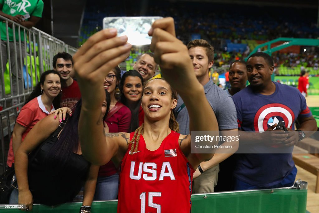 Brittney Griner of United States poses for a selfie with fans after defeating Spain in the women's basketball game on Day 3 of the Rio 2016 Olympic...