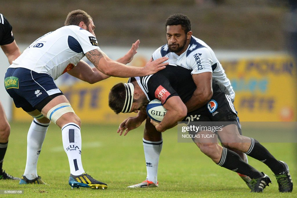 Brive's French centre Arnaud Mignardi (C) is tackled by Agen's New Zealand wing Georges Tisley (R) during the French Top 14 rugby union match between Agen and Brive on April 30, 2016 at the Armandie stadium in Agen, southwestern France.