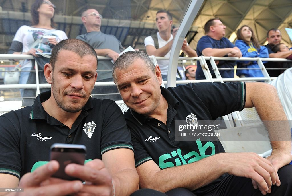 Brive's French coachs Nicolas Godignon (L) and Didier Casadei (R) look at a cellphone before the French Top 14 rugby match between ASM Clermont Auvergne and CA Brive on October 26, 2013 at the Marcel Michelin stadium in Clermont-Ferrand.