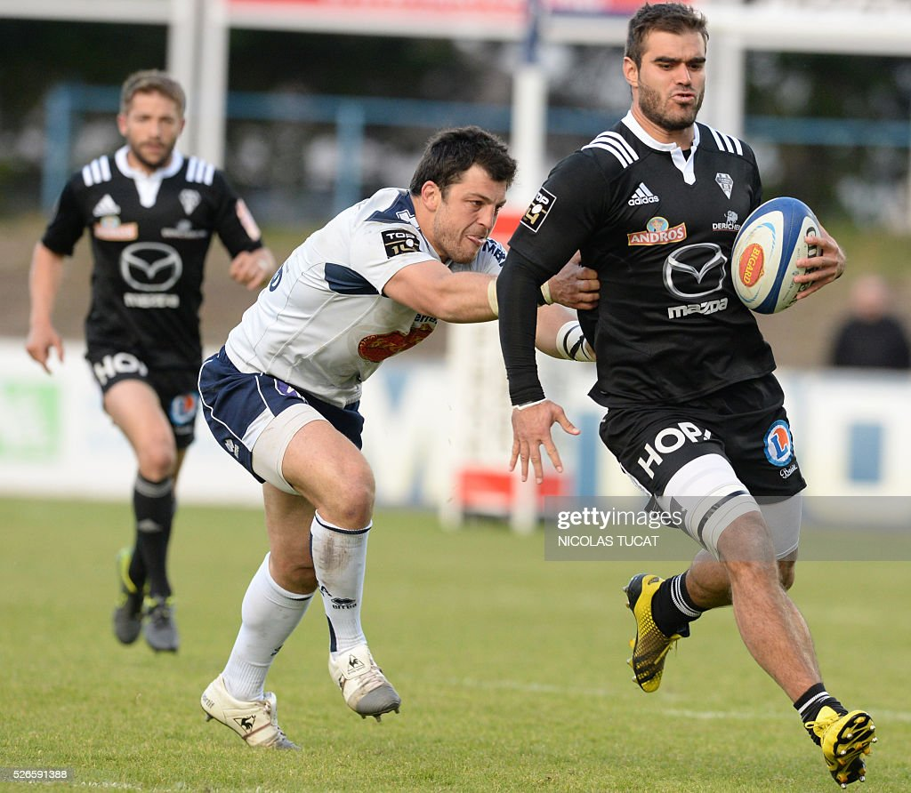 Brive's French fullback Gaetan Germain (R) is tackled by Agen's French centre Lionel Mazars (L) during the French Top 14 rugby union match between Agen and Brive on April 30, 2016 at the Armandie stadium in Agen, southwestern France.