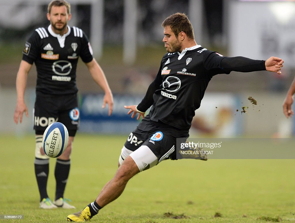 Brive's French fullback Gaetan Germain (R) kicks the ball during the French Top 14 rugby union match between Agen and Brive on April 30, 2016 at the Armandie stadium in Agen, southwestern France.