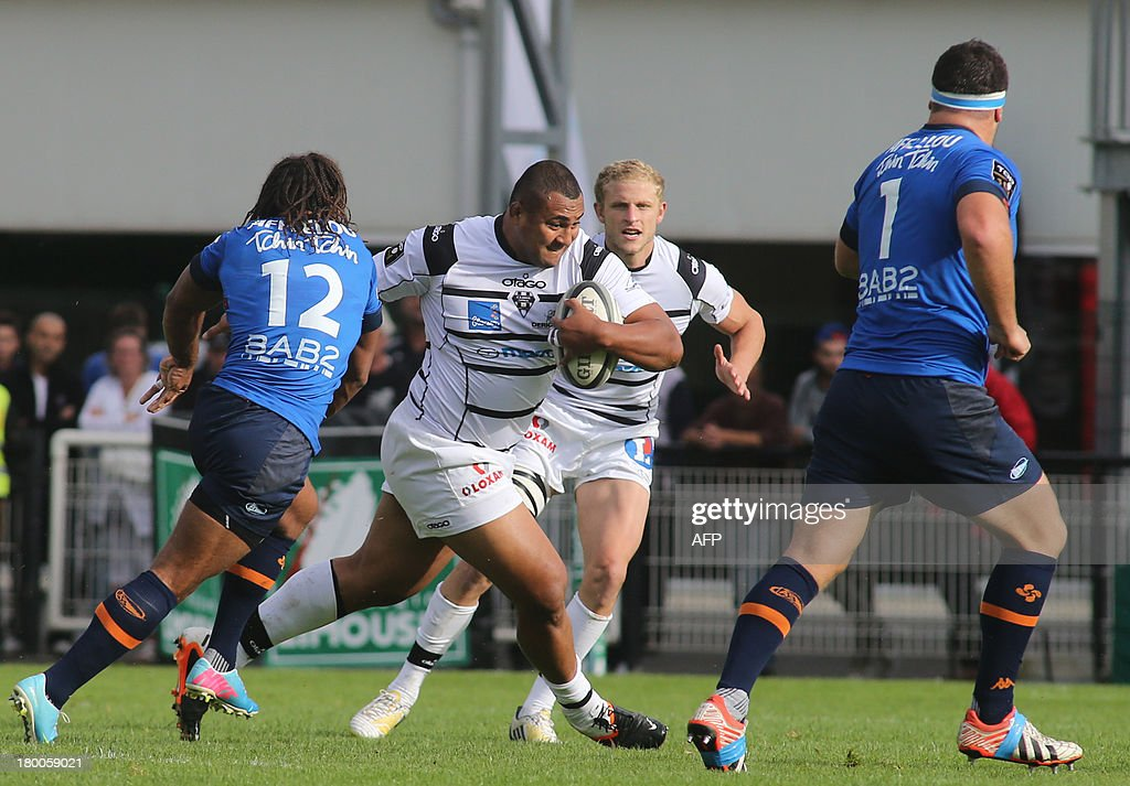 Brive's Sisaro Koyamaibole from Fiji (C) runs with the ball during the French Top 14 rugby union match C.A Brive versus Aviron bayonnais on September 8, 2013 at the Amedee Domenech stadium in Brive.