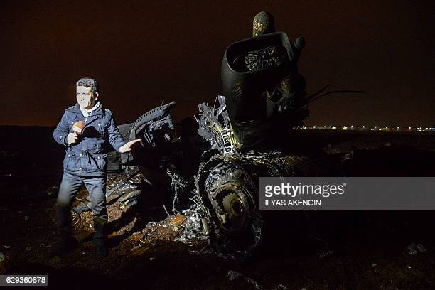 A broadcast journalist does a piece to camnera beside the wreckage of a Turkish F16 war plane which crashed in Diyarbakir on December 12 2016 A...