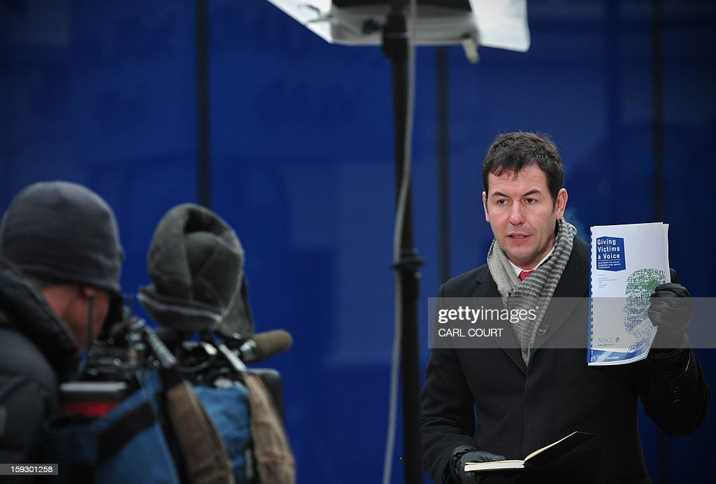 A broadcast journalist holds a copy of the report entitled 'Giving Victims a Voice' outside New Scotland Yard in central London on January 11, 2013. The report by the Metropolitan Police and NSPCC (National Society for the Prevention of Cruelty to Children) details 50 years of allegations of sexual abuse by former BBC presenter Jimmy Savile. British police said that late BBC star presenter Jimmy Savile was a predatory sex offender whose victims were as young as eight and who preyed on children and adults in hospitals and even a hospice. A report by police and child protection authorities found that the TV presenter, who was one of the biggest TV stars in Britain in the 1970s and 1980s, used his celebrity status to 'hide in plain sight'.