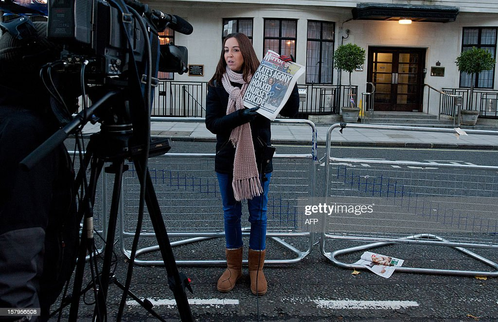 A broadcast journalist holds up a copy of a daily newspaper outside the King Edward VII hospital in central London on December 8, 2012 after nurse Jacintha Saldanha was found dead the previous day. A nurse at the hospital which treated Prince William's pregnant wife Catherine, Duchess of Cambridge, was found dead on December 7, days after being duped by a hoax call from an Australian radio station, the hospital said. Police said they were treating the death, which happened at a property near the hospital, as unexplained. AFP PHOTO / WILL OLIVER