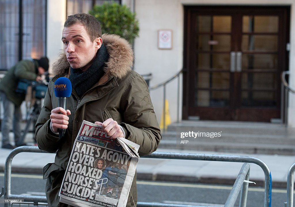 A broadcast journalist holds up a copy of a daily newspaper outside the King Edward VII hospital in central London on December 8, 2012 after nurse Jacintha Saldanha was found dead the previous day. A nurse at the hospital which treated Prince William's pregnant wife Catherine, Duchess of Cambridge, was found dead on December 7, days after being duped by a hoax call from an Australian radio station, the hospital said. Police said they were treating the death, which happened at a property near the hospital, as unexplained.
