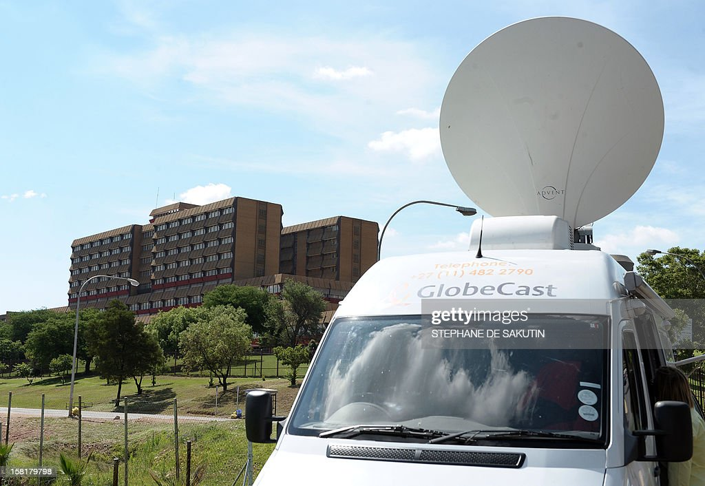 A broadcast vehicle is parked near the 1 Military Hospital (L) where South Africa's former President Nelson Mandela is hospitalised on December 10, 2012 in Pretoria. Ailing anti-apartheid Nelson Mandela was admitted to the hospital on December 8, 2012 to undergo tests and was said to be doing well. Mandela will remain in hospital for a third day tomorrow and receive further undisclosed tests, but was comfortable and in 'no immediate danger' the South African government said. Defence Minister Nosiviwe Mapisa-Nqakula visited Mandela earlier today and found the 94-year-old former president 'in good spirits.'AFP PHOTO / STEPHANE DE SAKUTIN