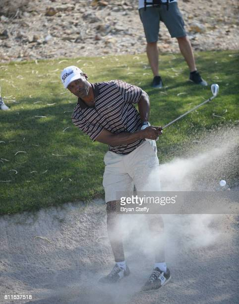 Broadcaster and former professional basketball player Eddie Johnson hits a sand bunker shot during the Coach Woodson Las Vegas Invitational at...