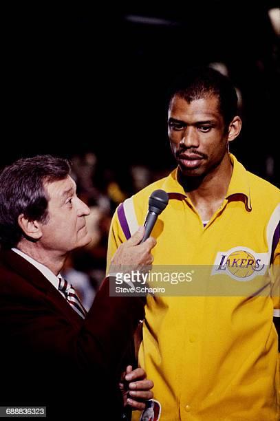 Broadcaster Chick Hearn left interviews Los Angeles Lakers basketball center Kareem Abdul Jabbar Los Angeles California 1984