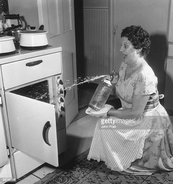Broadcaster Jill Summers of the television show 'Summers Here' directing a soda syphon into an oven to extinguish a fire