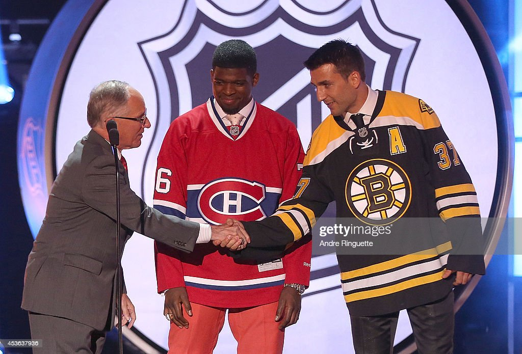 NBC broadcaster Mike Emrik (L) shakes the hand of <a gi-track='captionPersonalityLinkClicked' href=/galleries/search?phrase=Patrice+Bergeron&family=editorial&specificpeople=204162 ng-click='$event.stopPropagation()'>Patrice Bergeron</a> of the Boston Bruins onstage as <a gi-track='captionPersonalityLinkClicked' href=/galleries/search?phrase=P.K.+Subban&family=editorial&specificpeople=714418 ng-click='$event.stopPropagation()'>P.K. Subban</a> of the Montreal Canadiens looks on during the 2014 NHL Awards at the Encore Theater at Wynn Las Vegas on June 24, 2014 in Las Vegas, Nevada.