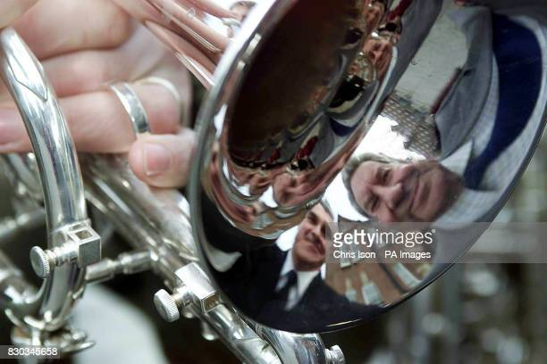 Broadcaster Richard Baker reflected in a trombone at the Royal Marines Band HQ in Portsmouth where he judged the contest to find a new march for the...