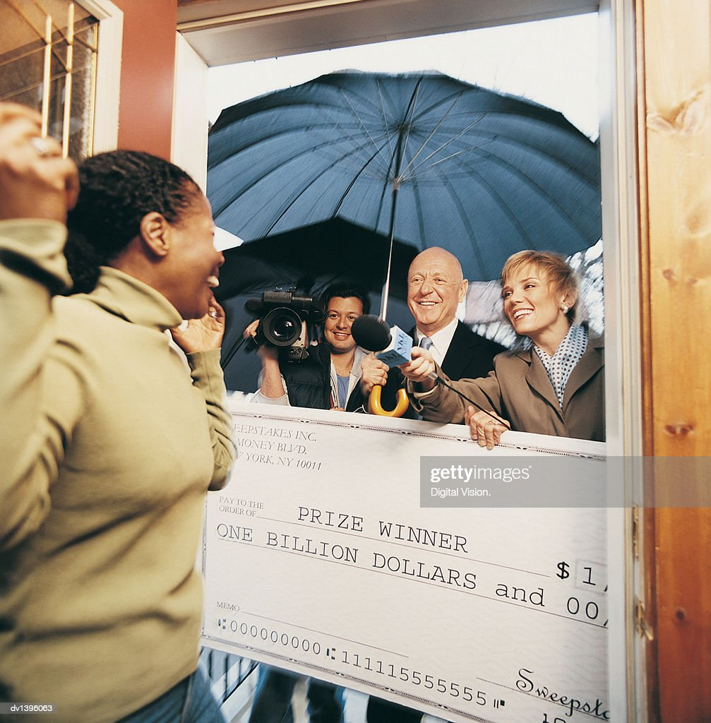 Broadcasters Present a Cheque to an Ecstatic Woman in her Home : Stock Photo