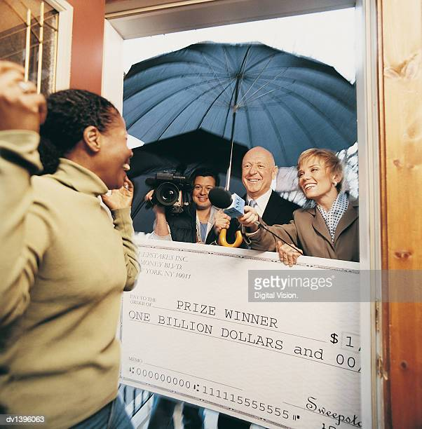 Broadcasters Present a Cheque to an Ecstatic Woman in her Home