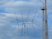 broadcasting and cell transmitter and receiver antenna and communication tower. symbolizing modern way of messaging and communications. tv signal receiving antenna. blue sky with clouds. steel truss t
