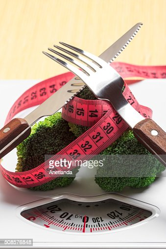 Broccoli with measuring tape on weight scale. Dieting : Stock Photo