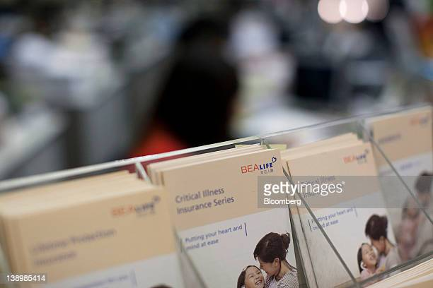 Brochures advertising insurance products are displayed on a counter in the Bank of East Asia Ltd main branch in Hong Kong China on Wednesday Feb 15...